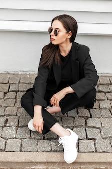 Bella giovane donna alla moda in occhiali da sole alla moda in bei vestiti neri per giovani in scarpe da ginnastica bianche alla moda si rilassa su piastrelle di pietra vicino a un edificio d'epoca in città. la ragazza alla moda in vestito alla moda gode del resto.