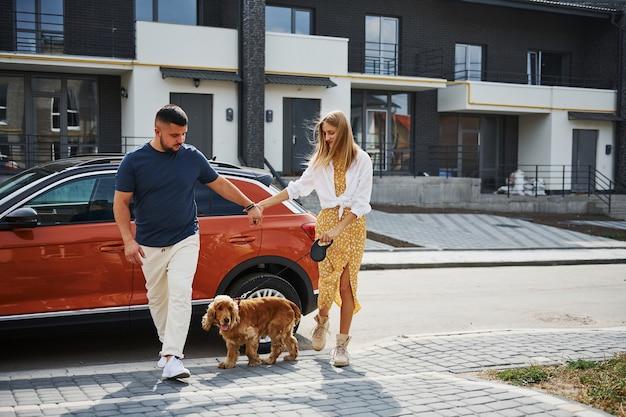 Una coppia adorabile fa una passeggiata insieme al cane all'aperto vicino alla macchina.