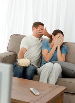Bella coppia che nasconde la loro faccia da un film dell'orrore seduto nel soggiorno