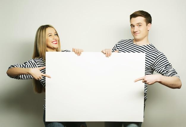 Bella coppia che tiene uno striscione - su uno sfondo grigio gray