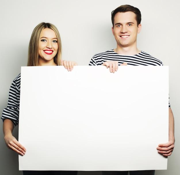 Bella coppia che tiene uno striscione - su uno sfondo grigio