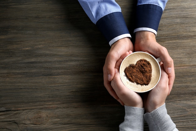 Coppie adorabili che tengono tazza di caffè in mani su fondo di legno