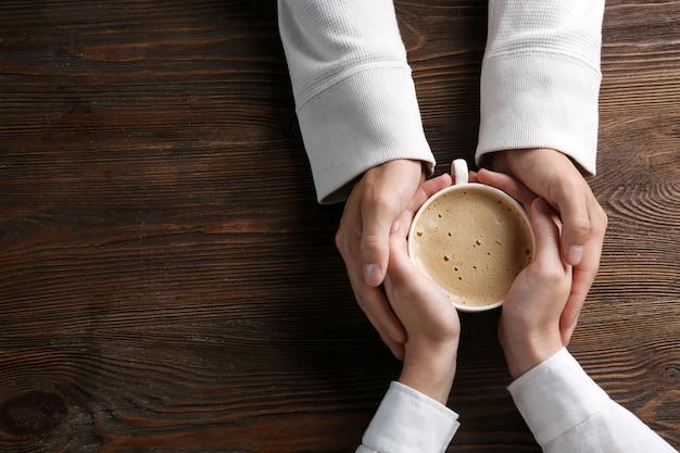 Coppie adorabili che tengono tazza di caffè nelle mani sulla tavola di legno
