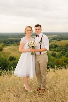Bella coppia di sposi in posa contro splendide vedute della natura verde. servizio fotografico pre-matrimonio