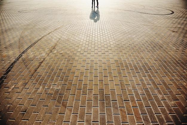 Bella coppia sulla piazza con pavimento in pietra sullo sfondo. foto di alta qualità