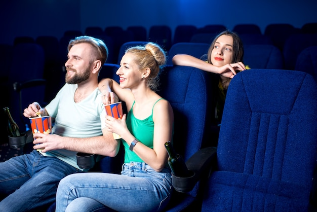 Bella coppia che guarda film seduti insieme a popcorn al cinema