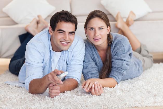 Bella coppia guardando la tv mentre sdraiato su un tappeto