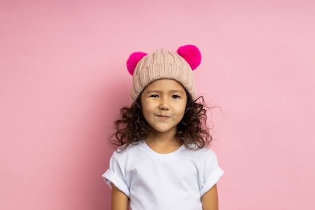 Adorabile bambina astuta che indossa una maglietta bianca, un cappello beige lavorato a maglia, sembra furba e astuta, sorride misteriosamente, ha un piano o un'idea interessante, in piedi. espressioni facciali.