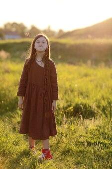 Bella ragazza carina che gioca all'aperto al tramonto, cammina e si diverte, infanzia felice. vacanza di sole estivo.