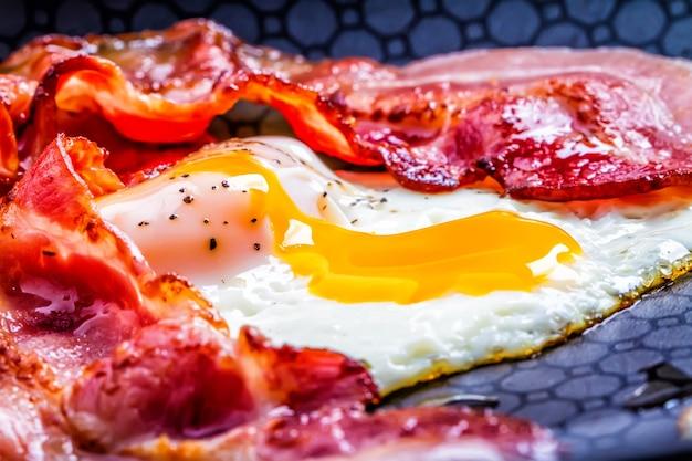 Prosciutto e uova deliziosi ed estremamente gustosi con tuorlo che cola e pancetta arrosto.