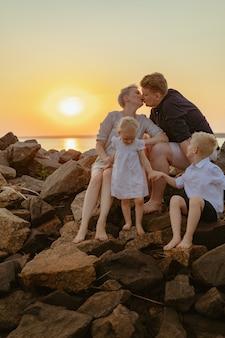 Bella famiglia donna incinta e suo marito che si baciano e i bambini si godono il tramonto sulla spiaggia
