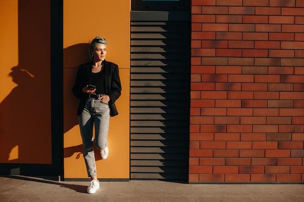 Bella signora alla moda con i capelli blu è sdraiata sul muro mentre tiene un cellulare e indossa gli occhiali