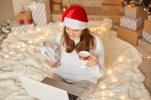 Bella femmina che ha videochiamata con la famiglia e mostra il regalo di natale alla telecamera, donna con cappello da babbo natale e maglione bianco con confezione regalo utilizzando laptop con web cam per salutare le persone vicine.