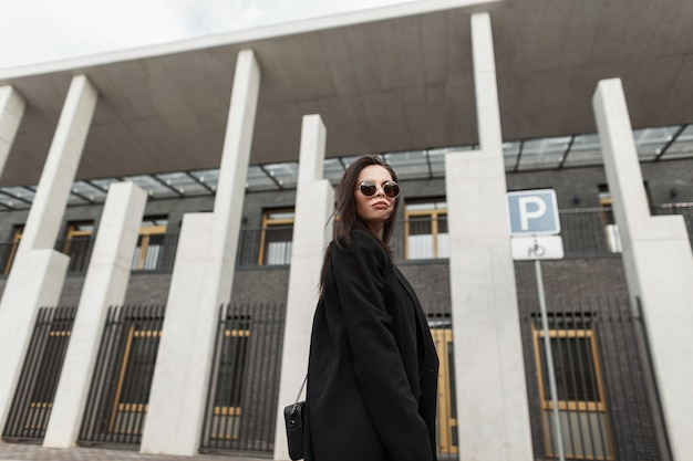 Bella giovane donna in occhiali da sole alla moda in un bellissimo blazer nero per giovani con borsa alla moda cammina vicino a un edificio moderno in città. bella ragazza abbastanza urbana in abbigliamento casual alla moda sulla strada.
