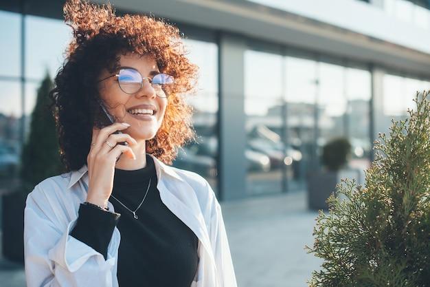 Una bella freelance con i capelli ricci sta discutendo al telefono mentre cammina fuori