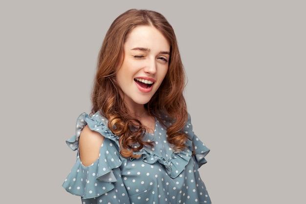 Bella e divertente ragazza bruna camicetta con volant che strizza l'occhio e flirta rallegrando l'aspetto giocoso