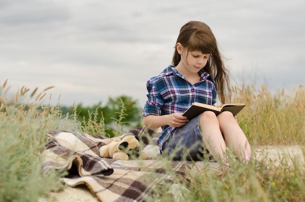 Adorabile bambina di 8 anni con lunghi capelli castani seduta su un plaid in una radura e legge un grosso libro