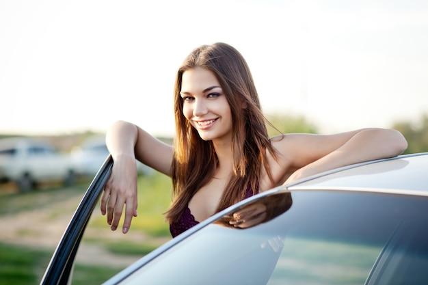 Bella ragazza vestita in biancheria intima viola, sorridente e, in posa vicino alla portiera della macchina aperta