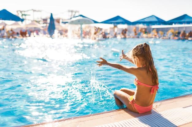 Una bella ragazza si siede sul bordo della piscina con i piedi immersi in acqua pulita e trasparente godendosi il caldo sole luminoso