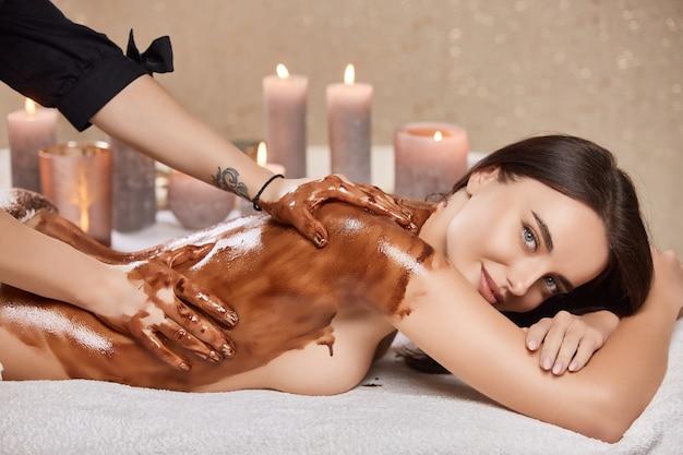 Bella ragazza nel salone della stazione termale con massaggio con maschera al cioccolato oleoso e candele