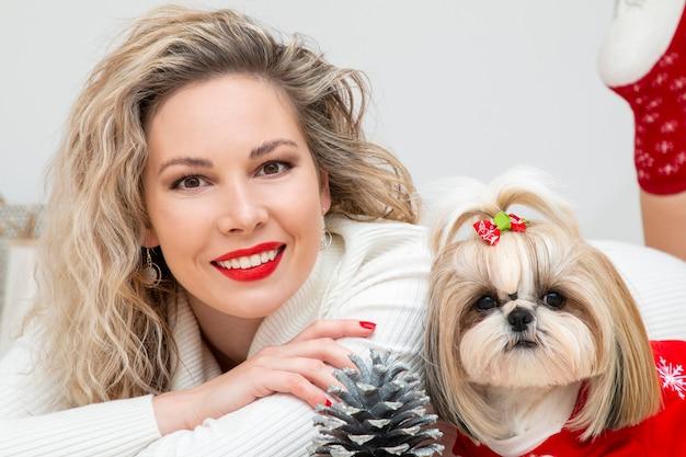 Una bella ragazza con un cucciolo shih tzu ben curato e ben vestito per natale
