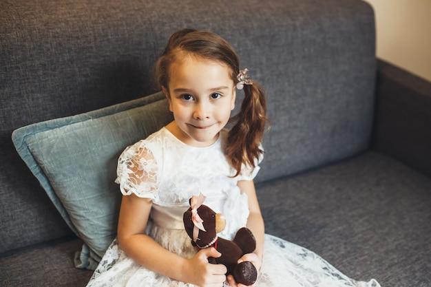 Bella ragazza con un abito bianco e un orsacchiotto in posa sul divano guardando davanti