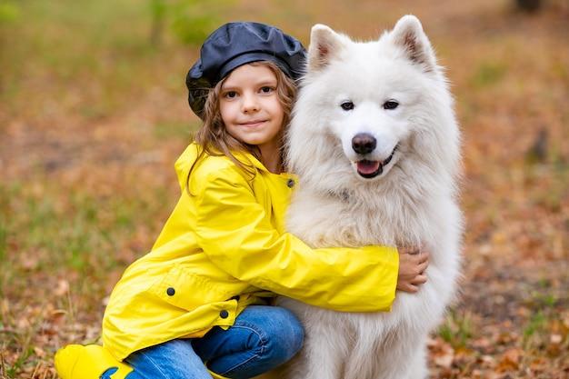 Bella ragazza in stivali di gomma gialli e impermeabile durante una passeggiata, gioca con un bellissimo cane samoiedo bianco nel parco d'autunno.