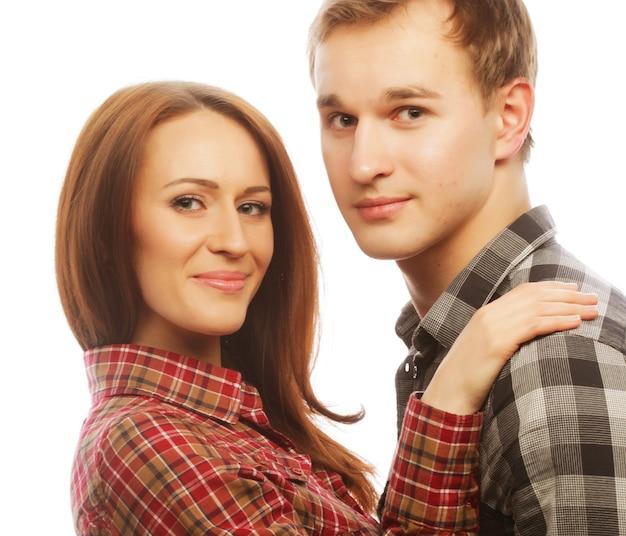 Bella coppia felice che abbraccia su sfondo bianco