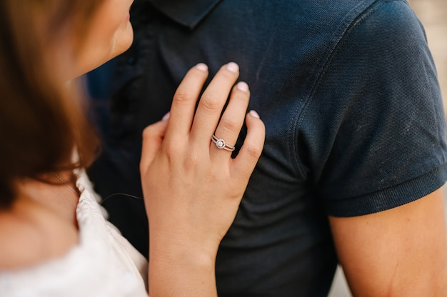La bella ragazza felice ha detto così e ha messo la mano con l'anello nuziale sul petto del suo ragazzo. amore, famiglia, concetto di anniversario.