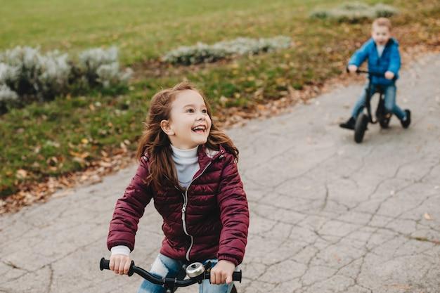 Bella bambina felice guardando i suoi genitori che ridono mentre va in bicicletta nel parco con suo fratello.