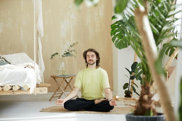 Uomo felice adorabile che medita a casa, maschio bello che si siede sulla stuoia di yoga che tiene le braccia in mudra di yoga e sorridente