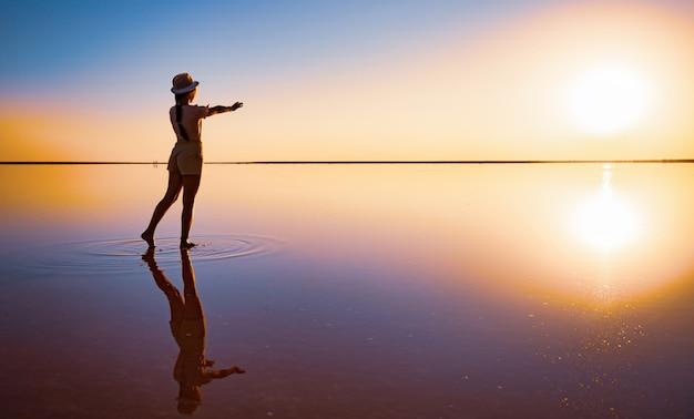 Bella ragazza felice cammina e posa in una posa magica lungo il lago salato rosa specchio godendosi il caldo sole serale, guardando il tramonto infuocato e il suo riflesso
