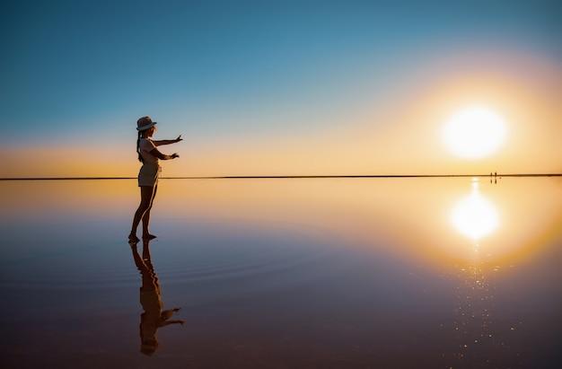 Bella ragazza felice che cammina e posa in una posa magica lungo il lago salato rosa specchio godendo il caldo sole serale, guardando il tramonto infuocato e il suo riflesso