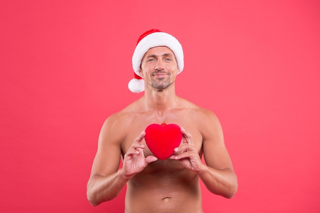 Cuore adorabile. cura della pelle. l'uomo bello celebra il fondo rosso di vacanze invernali. ragazzo indossa un cappello invernale. buon natale e felice anno nuovo. torso nudo dell'uomo maturo. corpo attraente. stagione invernale.