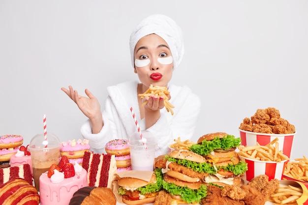 La casalinga adorabile tiene i palmi delle mani con patatine fritte soffia un bacio d'aria