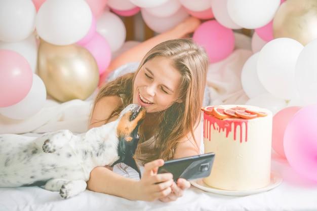 Bella signora in pigiama che fa selfie nella sua camera da letto usando il telefono e bacia il suo cane.