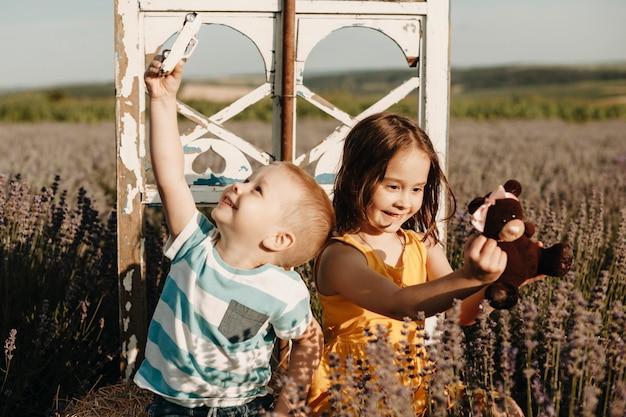 Ragazzino adorabile con la sua sorellina che gioca in un campo di fiori all'aperto.