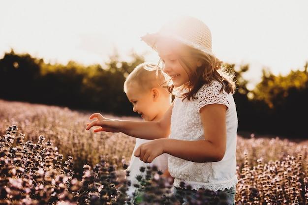 Bambina adorabile che ride mentre corre in un campo di fiori con suo fratello. piccolo bambino che gioca con sua sorella all'aperto contro il tramonto.