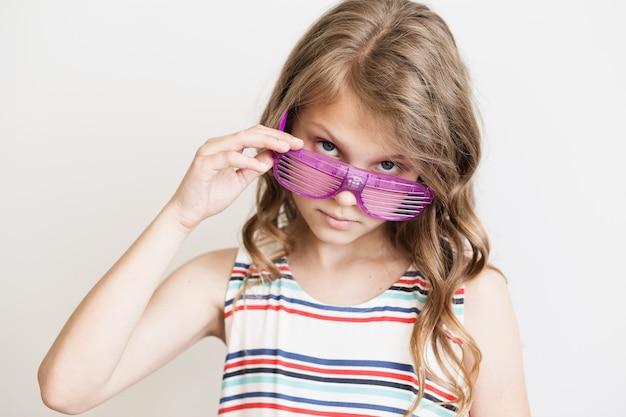 Bambina adorabile in un vestito a strisce con occhiali da sole a strisce di plastica divertenti del partito
