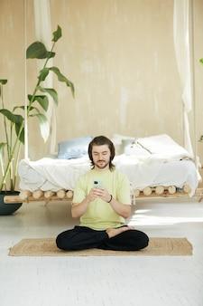 Uomo adorabile che si siede in asana di yoga utilizzando il telefono, insegnante di meditazione bello con i capelli lunghi sulla stuoia di yoga a casa che tiene smartphone