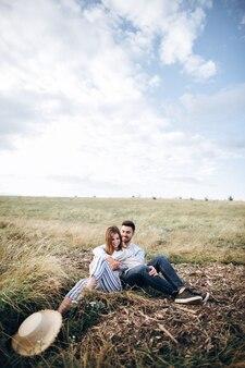 Bella coppia che si abbraccia, si bacia e sorride contro il cielo seduti sull'erba. spazio per il testo