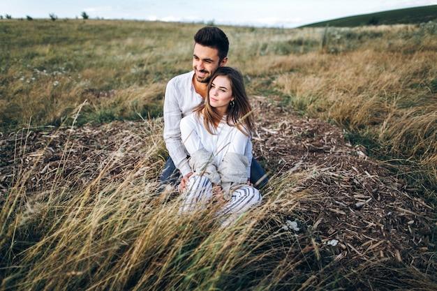 Adorabile coppia che si abbraccia, bacia e sorride contro il cielo seduti sull'erba