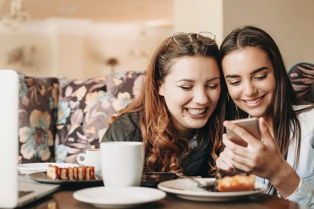 Bella donna plus size con i capelli rossi divertirsi a ridere con la sua amica mentre guarda lo smartphone in un caffè.