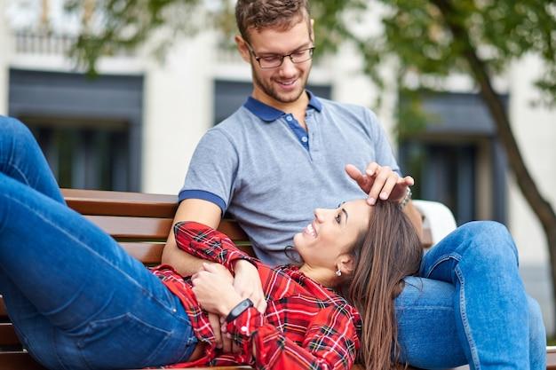 Bel ritratto di una giovane coppia. sono seduti sulla panchina, si abbracciano e si baciano.