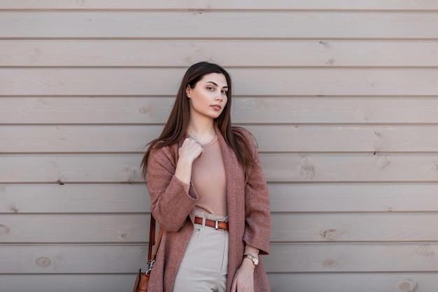 Bella bella giovane donna in cappotto alla moda in pantaloni con borsa marrone alla moda in pelle si trova vicino alla parete di legno vintage sulla strada. la bella ragazza attraente posa in città. vestito elegante alla moda primaverile.