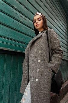 Modello adorabile della giovane donna graziosa in bandana alla moda in cappotto alla moda grigio in jeans dell'annata blu strappati con la borsa nera che posa vicino alla casa di legno verde all'aperto. ragazza di moda in abbigliamento elegante a piedi.