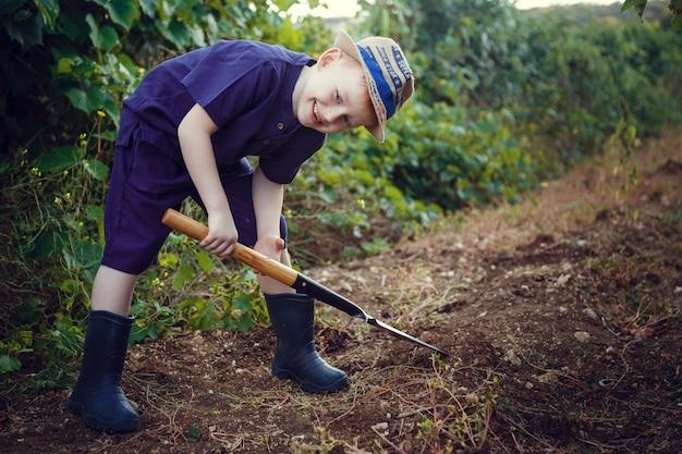 Un bel ragazzo dai capelli rossi con le lentiggini aiuta in giardino. l'idea e il concetto di scolarizzazione precoce per il lavoro nell'orto dei bambini