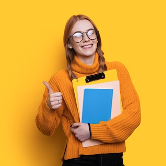Bella studentessa dai capelli rossi con le lentiggini che gestiscono il segno simile e che tengono le cartelle su una parete gialla