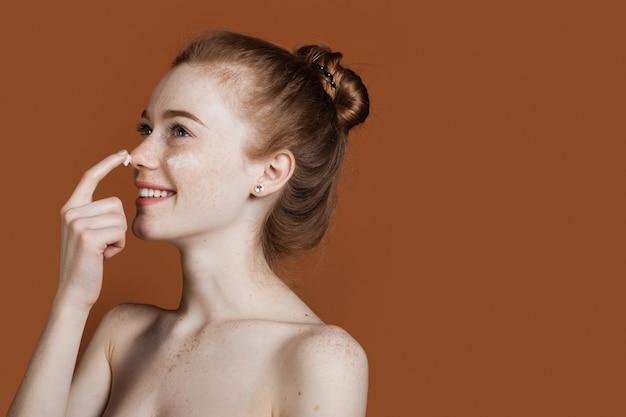 Bella donna dai capelli rossi con le lentiggini sta applicando una crema sul viso sorridente con le spalle svestite su una parete marrone dello studio