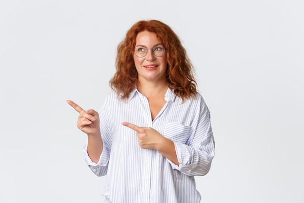Bella signora di mezza età dai capelli rossi, imprenditrice che sembra divertita e indica l'angolo in alto a sinistra. donna sognante anni '40 con gli occhiali sorridente, trovata ottima offerta, sconto speciale, muro bianco